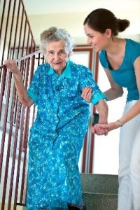 old women getting help walking down the stairs
